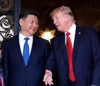 In this April 6, 2017 file photo, Chinese President Xi Jinping, left, smiles at U.S. President Donald Trump as they pose together for photographers before dinner at Mar-a-Lago in Palm Beach, Fla.  (AP Photo/Alex Brandon)