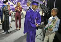 14-year-old Carson Huey-You smiles as his 10-year-old brother Cannan shows him one of his graduation gifts, a Hobbit Lego set, after Carson received a bachelor's degree in physics at TCU (Louis DeLuca/Dallas Morning News)