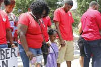 Jordan Edwards' step-mom Charmaine Edwards, sister Korrie Edwards, 4, and dad, Odell Edwards, bow their heads in prayer in front of the Frank Crowley Courts Building Saturday May 13, 2017 during a rally remembering Jordan and others killed by police.(Ron Baselice/Staff Photographer)