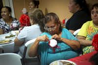 Maria Perez pins a flower to her blouse during the the city's annual Mother's Day Dinner at city hall on May 10, 2017, in El Cenizo, Texas.(Smiley N. Pool/The Dallas Morning News)