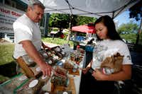 Rick Stricklin, left, of the Sprout Stand, talks to Catherine Nguyen at the McKinney Farmers Market.(ANJA SCHLEIN/Special Contributor)