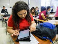 Claudia Hernandez works on her school district-issued iPad at Garland High School. The district spent $15.5 million to deploy 16,300 devices to high school students as part of the Garland ISD 1:1 Ready initiative. (Ashley Landis/The Dallas Morning News)