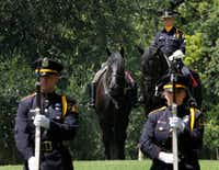 Dallas Police officer Ron Cunningham sits with a riderless horse as 21 Gun Salute officers file in formation during Wednesday's memorial service for fallen peace officers. (David Woo/The Dallas Morning News)(David Woo/Staff Photographer)