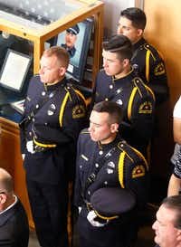 Dallas Police Officers stand at attention next to a display case honoring DART Police Officer Brent Thompson during the DART Police Department memorial service held in honor of National Police Memorial Week  at DART police headquarters on Thursday.(Ron Baselice/Staff Photographer)