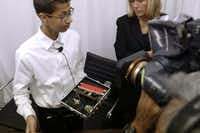 """Clock Boy"" Ahmed Mohamed shows the clock he built in a school pencil box after a news conference with family's attorney Susan E. Hutchison, right, in Dallas on Aug. 8, 2016. (David Woo/The Dallas Morning News)"