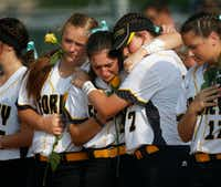 Forney softball players Sam Coker (1, left) and Savannah DesRochers (2, right) embrace Caroline Tedder (30, middle) during a moment of silence for their teammate Emily Galiano before the regional semifinal game against Mansfield Lake Ridge at Kennedale High School in Kennedale, Texas on May 18, 2017. (Rose Baca/Staff Photographer)