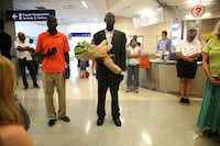 Abraham But (center) waits at the international arrivals gate with cousin Philip Machok for his mother, Nyak Marol Kur. <br>(Rose Baca/Staff Photographer)