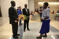 Abraham But (far left) and his cousin Philip Ayuen (center) pause to pray with But's mother Nyak Marol Kur as But saw her for the first time in 30 years at DFW International Airport. <br>(Rose Baca/Staff Photographer)
