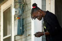 Thelma Jean Williams, 64, checks her phone after listening to a news conference at her neighbor's rent house. Williams says she would like to purchase a rent house, too.(Tom Fox/Staff Photographer)