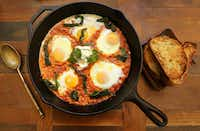 Eggs poached in spiced tomato-harissa sauce(Louis DeLuca/Staff Photographer)