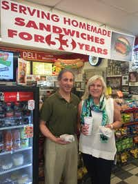 Randy and Paige Flink hold their fresh-off-the-grill burgers at Parkit Market. The Greenville Avenue convenience store and deli has been in business at the same location for more than 50 years.(Courtesy Paige Fink)