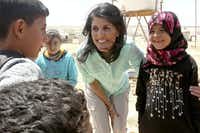 "U.S. Ambassador to the United Nations Nikki Haley, speaks with Syrian refugee children, during a visit to the Zaatari Refugee Camp, Jordan, Sunday, May 21, 2017. Haley said the Trump administration wants to step up help for the millions of people displaced. Yet Nikki Haley's message is at odds with President Donald Trump's ""America First"" agenda, his planned budget cuts and his hardline position on admitting refugees.(Raad Adayleh/AP)"
