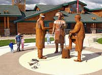 In this June 21, 2004 file photo, visitors walk past the figures of Chief Sheheke, left, Meriwether Lewis, center, and William Clark being installed in front of the Lewis and Clark Interpretive Center in Washburn, N.D. On Wednesday, May 24, 2017, a foundation announced it has transferred a nearly $700,000 endowment trust to support maintenance at the center. The state took over the center's operations from the financially troubled foundation two years ago. (Tom Stromme/The Bismarck Tribune via AP, File)(Tom Stromme/AP)