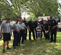 <p>Graham Day, 8, with a Hurst police officers and firefighters who celebrated his birthday with him after no one showed up for his party.</p>(Facebook)