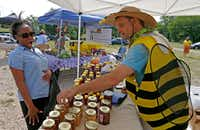 Brandon Pollard (right) talks with Natalie Steward about honey products at Texas Honeybee Guild's booth at the farmers market on the Paul Quinn College campus.(Jae S. Lee/Staff Photographer)
