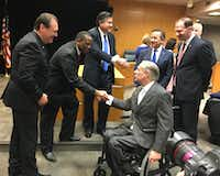 Gov. Greg Abbott shakes hands with executive commissioner of health and human services Charles Smith as protective services chief Hank Whitman, left, looks on. In background are four of nine lawmakers who joined the governor at a CPS bill signing -- from left, Rep. Richard Raymond, Sen. Carlos Uresti, Sen. Charles Schwertner and (partially obscured) Rep. James Frank.(Robert T. Garrett/Staff)