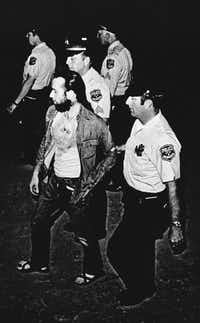 """In this Friday, July 22, 1972 file photo, Milwaukee Police officers lead comedian George Carlin off the Summerfest grounds in Milwaukee, Wis. He was arrested after his act which included """"The Seven Words You Can Never Say on Television,"""" a social commentary about censorship.(File photo/The Associated Press)"""