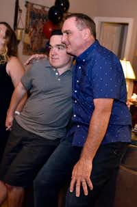 Ryan Dant, 29, hugs his dad, Mark Dant, after a toast wishing Ryan good luck. His college graduation party was held at a family friend's house in Carrollton on Friday. (Ben Torres/Special Contributor)
