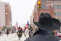 "A Fort Worth police officer looks on during the Fort Worth Stock Show's ""All Western Parade"" earlier this year. Cowboy hats are a normal part of the department's uniforms.(Lawrence Jenkins/Special Contributor)"
