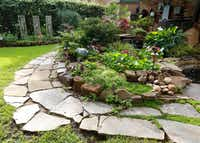 Kimberly Atchley placed the stones and planted the flowers in her backyard pond at her Richardson home.(Ron Baselice/Staff Photographer)