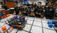 Anthony Vargas, 9, (from left) Hector Martinez, 11, Abelino Graciano, 11, and Keyri Fernandez, 11, work together to balance The Flash (left) and Wildbot on a ramp during robotics club at Winnetka Elementary in Dallas on May 26, 2017.(Nathan Hunsinger/Staff Photographer)