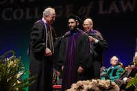 Law student Rafael Valbuena stands on stage during UNT Dallas' first Juris Doctor hooding ceremony on May 20 alongside Dean Royal Furgeson (left) and professor Thomas Perkins. (UNT-Dallas College of Law)