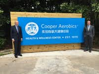 Ken Cooper and his son Tyler Cooper pose with a sign at Cooper Aerobics Health and Wellness Center China(Cooper Aerobics Center)