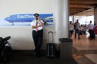 Southwest Airlines' senior pilot Lou Freeman, the first African-American chief pilot of a major U.S. airline, chats on the phone before boarding his final flight at Dallas Love Field airport on Thursday.(Rose Baca/Staff Photographer)