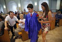 "<p><span style=""font-size: 1em; background-color: transparent;"">Zack Thibodeaux honored his mother Johanna Uek with a rose as his step-father Joey Uek (left) leans in to congratulate him on his 8th grade graduation.</span></p>(Tom Fox/Staff Photographer)"