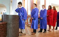 Zach makes the sign of the cross after taking holy water as he enters Mary Immaculate Catholic Church for his eighth-grade graduation.(Tom Fox/Staff Photographer)