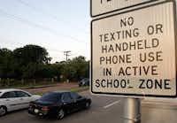 Cars pass through a school zone at Camp Wisdom Road and Wilcox Drive in Dallas. A state law bans the use of mobile devices in school zones.(File Photo/The Dallas Morning News)