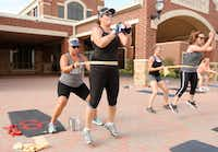 Tina Pearson (left) helps Rhonda-Lee Foulds work out at a Camp Gladiator session in Roanoke. Foulds, who has completed 59 marathons, fights her diagnosis of Parkinson's disease with daily exercise.  (Ron Baselice/Staff Photographer)