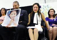 Jimmy Greene and Nelba Marquez-Greene, parents of Sandy Hook Elementary School shooting victim Ana Marquez-Greene, and Nicole Hockley (right), mother of victim Dylan Hockley, supported one another during a news conference at Edmond Town Hall in Newtown, Conn., in January 2013, a month after the mass shooting. (File Photo/The Associated Press)