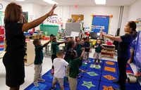 Onjaleke Brown, principal at N.W. Harllee Early Childhood Center in Dallas, left, participates in a song with pre-K teacher Librada Gil and her students. (David Woo/Staff Photographer)