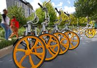 People walk by VBikes at Klyde Warren Park in Dallas. (Jae S. Lee/The Dallas Morning News)