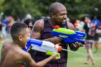 Jaylen Mayo, 8, and his dad, Ahmad Mayo, both of Denton, Texas, participate in a massive water gun fight hosted by Dallas Flash Mob in September 2015 at Klyde Warren Park in Dallas.(Ashley Landis/Staff Photographer)