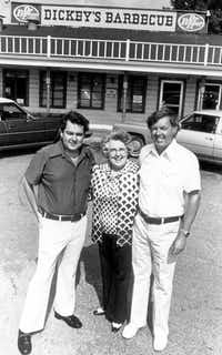 """Roland Dickey (left) and Travis """"TD"""" Dickey Jr. stood with their mother, Ollie Dickey, in front of the original Dickey's Barbecue Pit on North Central Expressway and Henderson Avenue in 1976.(Dickey's Barbecue Restaurants)"""