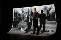 <p><i>Dallas Morning News</i> multiplatform editor Frank Christlieb stands before a large projection of his birth  father, Bob Workman, whom he never met but learned about as he researched his birth family.  (Tom Fox/Staff Photographer)</p>