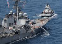 The damaged USS Fitzgerald is seen near a tugboat off the Shimoda coast after it collided with a Philippine-flagged container ship.(Agence France-Presse)