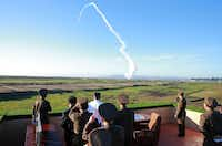 This undated picture released from North Korea's official Korean Central News Agency on May 28, 2017 shows North Korean leader Kim Jong-Un (C-in white shirt) watching the test of a new anti-aircraft guided weapon at an undisclosed location.(AFP/Getty Images)
