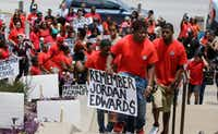 Slain teen Jordan Edwards' brother Vidal Allen (front) led his family up the courthouse steps during a protest in Dallas in May. Balch Springs officer Roy Oliver was fired and charged with murder after fatally shooting Jordan, a teenage passenger in a car trying to leave a house. A growing number of law enforcement agencies, including the U.S. Department of Justice, either deeply discourage or prohibit shooting at a moving car unless someone inside is shooting back.(LM Otero/The Associated Press)