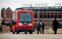 Alliance for Transportation Innovation's  EZ-10, a six-seat self-driving shuttle, ferries passengers from a set location on a closed course near Globe Life Park in Arlington earlier this year. In a few weeks, the vehicles are expected to go live at Rangers games.(Tom Fox/Staff Photographer)