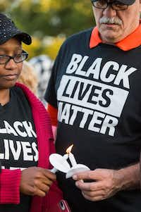 Monica Tunstle-Garrett (left) helps Al Woolum light a candle during a vigil for Jordan Edwards, a 15-year-old freshman at Mesquite High School who was shot and killed by a Balch Springs police officer.(Smiley N. Pool/Staff Photographer)