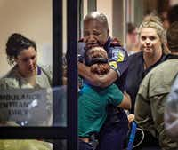 A DART police officer receives comfort at Baylor University Hospital emergency room entrance after the downtown ambush. (Ting Shen/Staff Photographer)