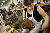 Yolanda Olvera laces together a new hand-made Nokona baseball glove at Nocona Athletic Goods.(TOM FOX/Staff Photographer/The Dallas Morning News)