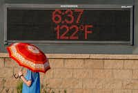 A pedestrian uses an umbrella to get some relief from the sun as she walks past a sign displaying the temperature on June 20, 2017 in Phoenix, Arizona.(Ralph Freso/Getty Images)