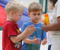 Flynn Willis (left) and Teak Noles apply sunscreen as they play outside at Children's Learning Adventure in McKinney. (Ron Baselice/Staff Photographer)