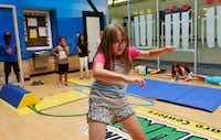 Natalie Summers, 9, counts to 10 at the hula-hoop station as she participates in a small obstacle course race in the Children's Learning Adventure gym in McKinney. The company is expanding  with new campuses coming to Allen and Flower Mound.(Ron Baselice/Staff Photographer)