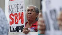"""Protesters gather outside the Federal Courthouse to oppose a new Texas """"sanctuary cities"""" bill that aligns with the president's tougher stance on illegal immigration on Monday in San Antonio.(Eric Gay/AP)"""
