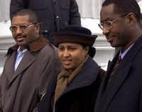 Kadiatou Diallo is flanked by her brothers as she arrives to the courthouse for the murder trial of four police who opened fire on Diallo's son, Amadou.(Ozier Muhammad/The New York Times)